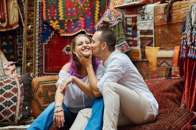 Couple in love chooses a turkish carpet at the market. cheerful joyful emotions on the face of a man and a woman