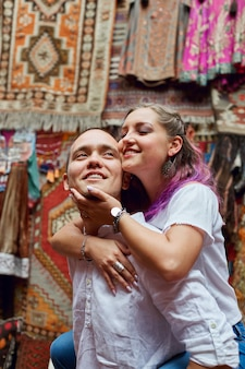 Couple in love chooses a turkish carpet at the market.