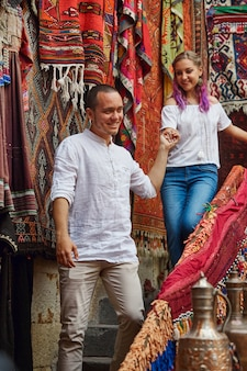 Couple in love chooses a turkish carpet at the market. Premium Photo