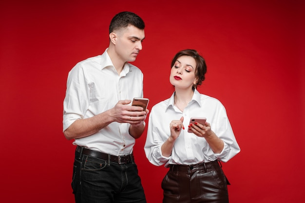 Couple in love communicates with each other, picture isolated on red wall
