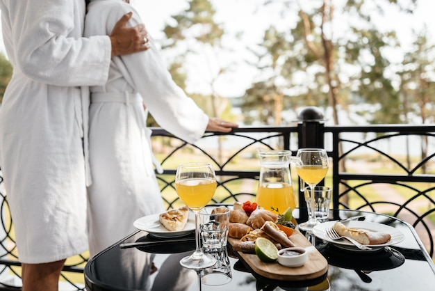 A couple in love cuddling on a hotel balcony in their bathrobes with breakfast on the table close up