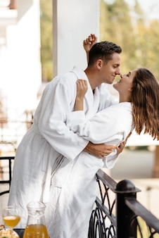 A couple in love cuddling on a hotel balcony in their bathrobes with breakfast on the table