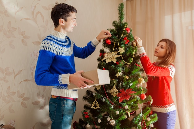 Couple in love decorating christmas tree at home, wearing winter sweaters. preparing to new year