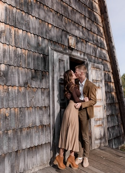 Couple in love dressed in casual clothes is kissing near the front door of a wooden building outdoors