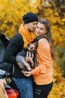 Couple in love embrace in an autumn park with a dog