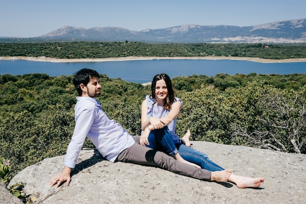 Couple in love enjoying a nice spring day in the countryside overlooking a large lake