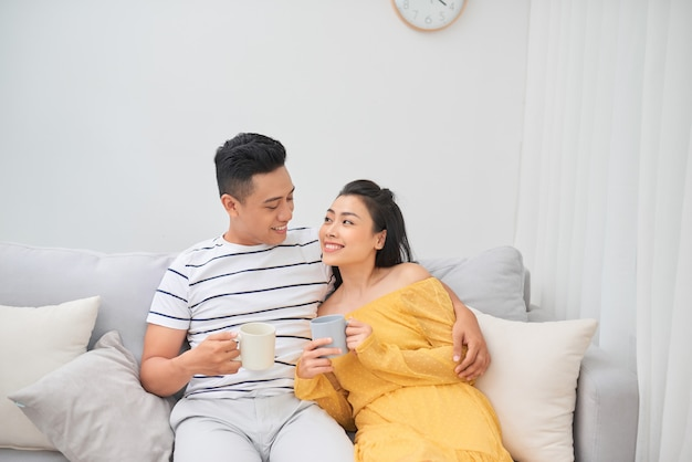 Couple in love enjoying their free time, sitting on a couch,drinking coffee and chatting.