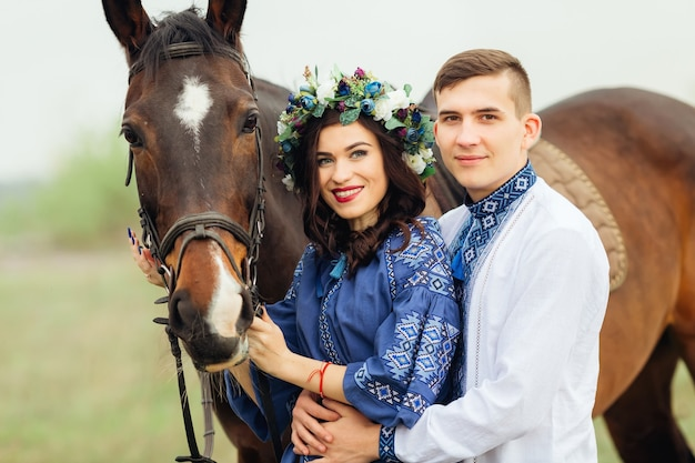 A couple in love in festive clothing stands near the horse