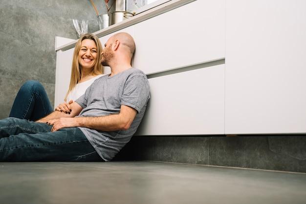 Coppia in amore sul pavimento in cucina