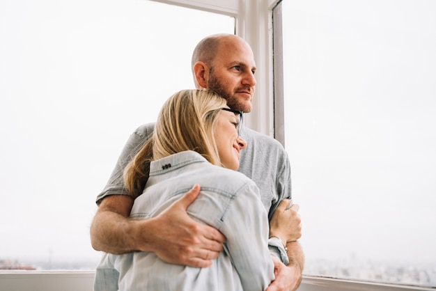 Couple in love in front of window