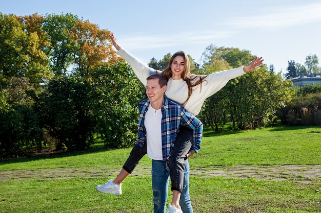 Couple in love in a good mood having fun in the autumn park. young couple in the park