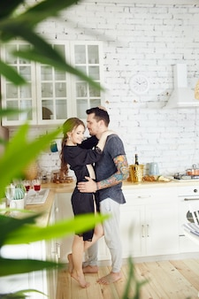 Couple in love has breakfast in the kitchen early in the morning. hugs and kisses, sexy woman in bathrobe and man. weekend morning in the kitchen