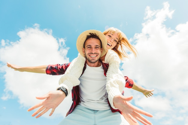 Couple in love having fun outdoor - friends playing piggyback on a blue sky