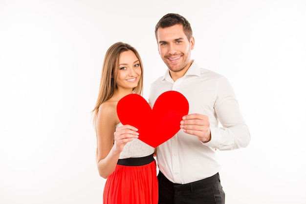 Couple in love holding big paper heart