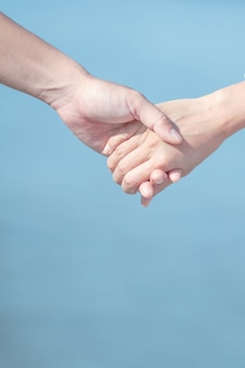 Couple love holding hands on blue sky and sea background.