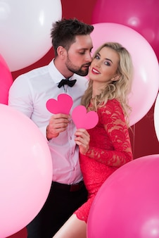 Couple in love holding pink hearts made of paper