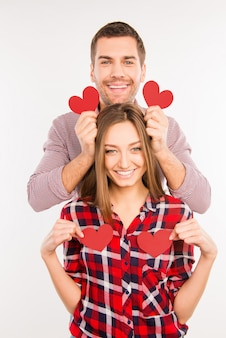 Couple in love holding red paper hearts