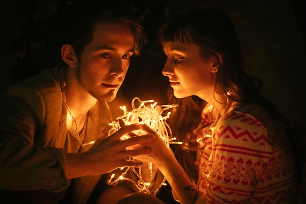 Couple in love hugging by night before christmas. loving embrace, light christmas garland. guy and girl love each other.
