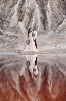 Couple in love hugging, mountains and red lake