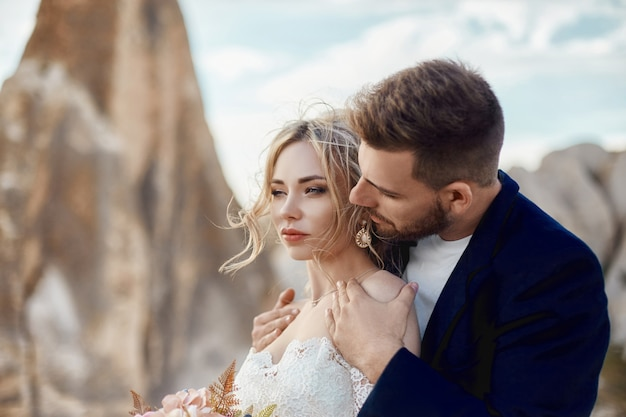 Couple in love hugs and kisses in fabulous mountains in nature. girl in long white dress with bouquet of flowers in her hands, man in jacket. wedding in nature, relationships and love