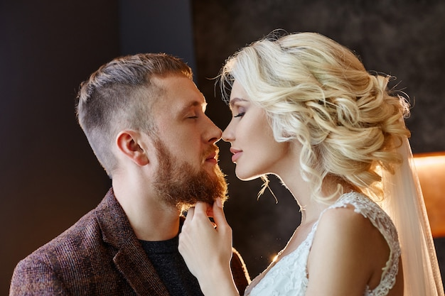 Couple in love hugs and kisses on their wedding day. hipster groom and the bride, love and loyalty. ideal couple is preparing to become husband and wife. man and woman looking at each other close up