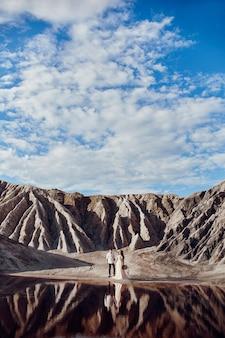 Влюбленная пара в сказочных горах, обнимающихся возле красного озера, сказочные пейзажи. влюбленные гуляют летом по горам, девушка в длинном легком летнем платье с букетом цветов и венком на голове