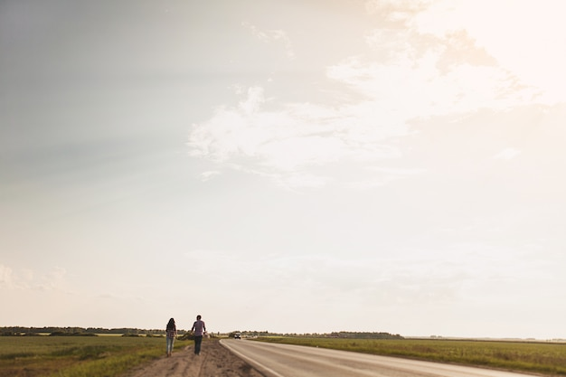 Couple in love is on a country road. the concept of hitchhiking. rear view. copy space for text.