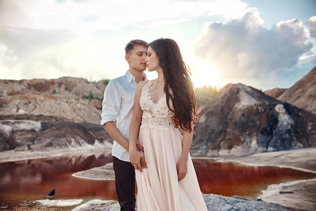 Couple in love kissing and hugging on the backdrop of fabulous mountains