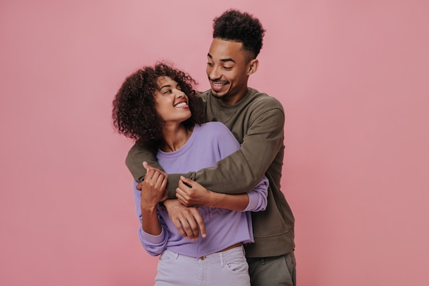 Couple in love looking at each other with love and smiling on pink wall