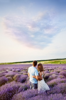 Couple in love looks at the picturesque landscape. lavender field. sunset. cloud in the form of a heart.