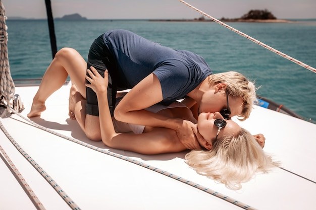 Couple in love lying on their white expensive yacht.