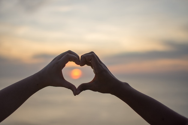 Couple love make sign hand of heart with sunset. subject is blurred.