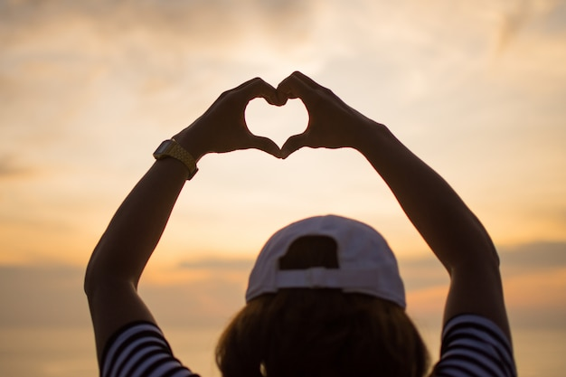 Couple love make sign hand of heart with sunset.