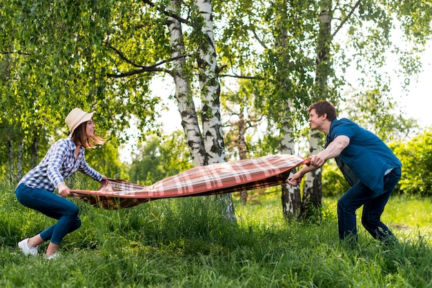 Couple in love placing picnic blanket on meadow