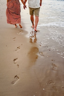 Couple in love playing and walking on the shore of the beach.