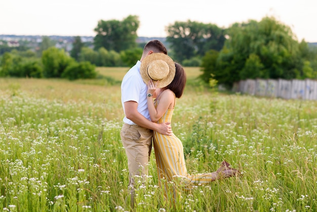Couple in love posing in nature among wildflowers in summer