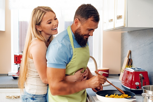 Couple in love preparing meal together in kitchen