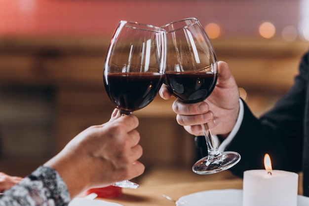 Couple in love raises glasses of red wine