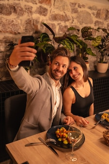 Couple in love in a restaurant, having fun dining together, celebrating valentine's day, taking a souvenir selfie. vertical photo