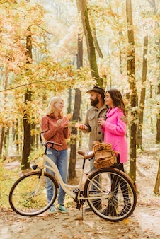 Couple in love ride bicycle together in forest park. friends with bicycle. bearded man and women relaxing in autumn forest. romantic couple on date. date and love. autumn date hike in forest