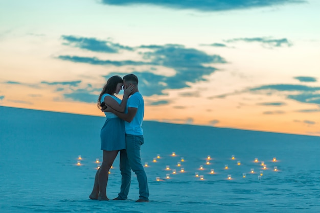 Couple in love romantic hugs in sand desert, evening, romantic atmosphere, in sand burn candles