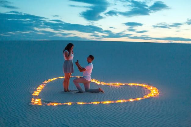 Couple in love romantic hugs in sand desert.