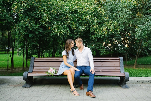 Couple in love sit on a bench in the park in the summer and have fun