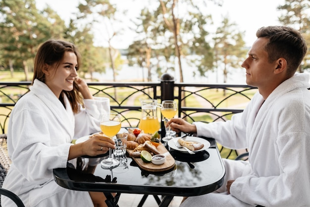 A couple in love sitting on a hotel balcony in their bathrobes with breakfast on the table