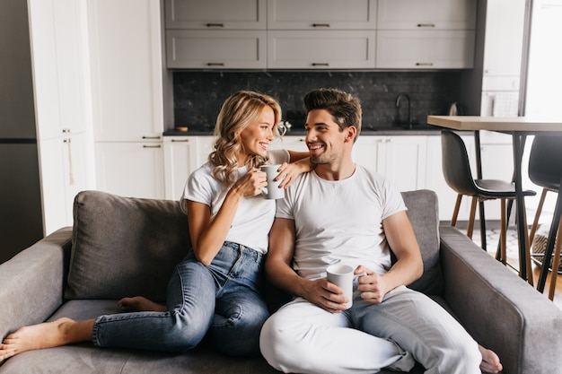 Couple in love sitting on sofa holding cups looking at each other and smiling. romantic couple enjoys morning together at home.