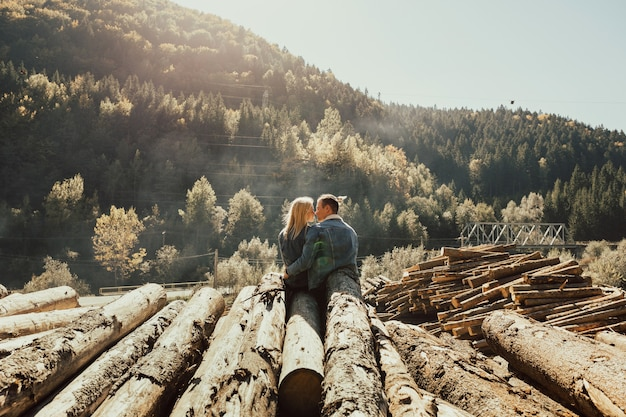 Couple in love sitting on the stack of firewood