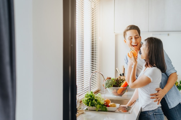 Couple in love smiling and have fun while cooking in kitchen