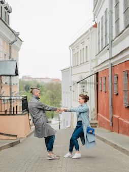 Couple in love spinning holding hands, on a city street, spring, dressed in a long coat