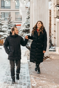 A couple in love stroll through the snowy city holding hands
