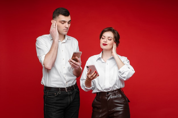 Couple in love surfing internet and talk with imaginary phones, picture isolated on red wall